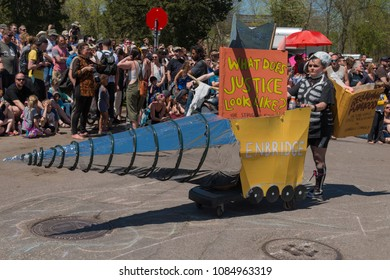 MINNEAPOLIS - May 6, 2018: A woman promotes leftist literature and demonstrates against energy company Enbridge during Minneapolis' yearly May Day parade.