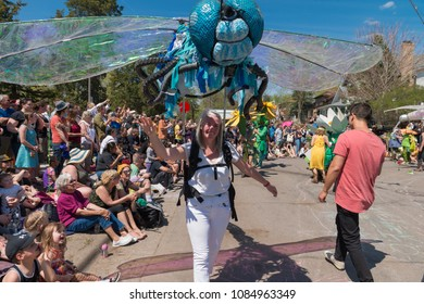 MINNEAPOLIS - May 6, 2018: A woman walks with a giant dragonfly puppet in Minneapolis' yearly May Day parade, organized by In the Heart of the Beast Puppet and Mask Theatre.