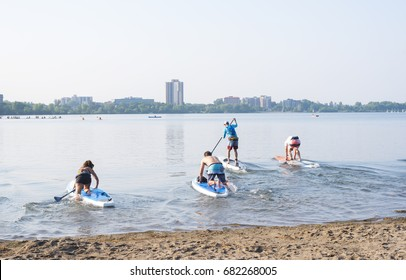 Minneapolis, Minnesota, United States - July 20, 2017: Group of people at start of paddle board race at Lake Calhoun.
