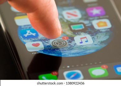MINNEAPOLIS, MINNESOTA / USA - APRIL 25, 2019: Person using Apple i-phone to press and access the Settings app / application