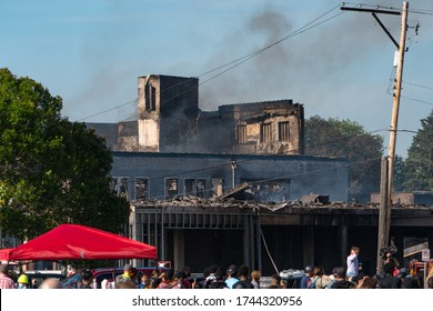 Minneapolis, Minnesota/United States of America - May 28, 2020: The remains of a burned building continue to smoke as protestors gather near the Third Precinct in Minneapolis.