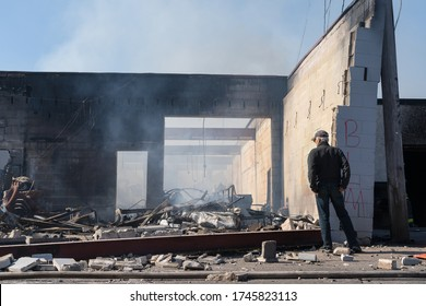Minneapolis, Minnesota/United States of America - May 30, 2020: A business owner surveys the damage done to his building after it was set on fire during a night of rioting in Minneapolis.