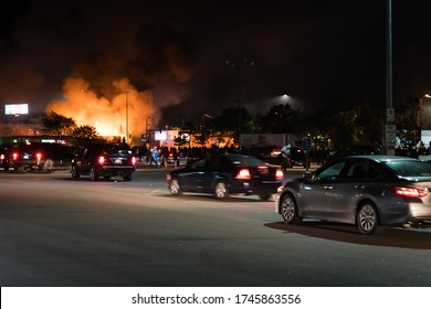 Minneapolis, Minnesota/United States of America - May 29, 2020: Cars show up at a parking lot to join with protestors as a building burns in the background following the death of George Floyd.