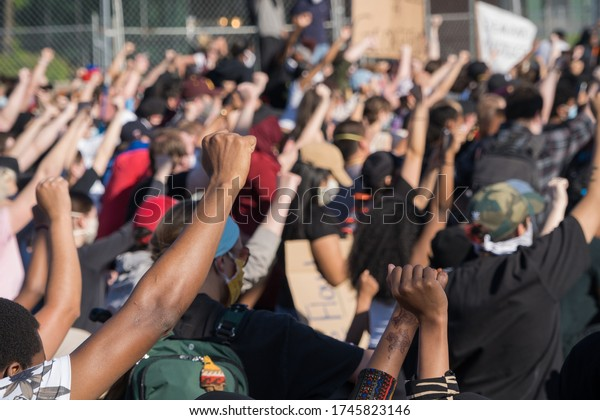 Minneapolis, Minnesota/United States of America - May 30, 2020: Protestors raise their hands in solidarity outside of the Fifth Police Precinct in Minneapolis in response to the death of George Floyd.
