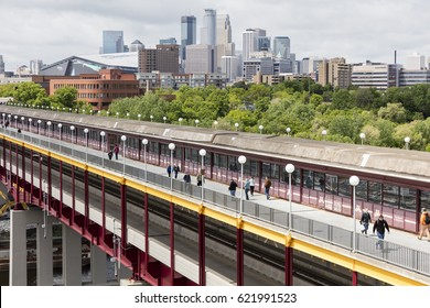 Minneapolis, MN - 13 May 2016 : Students crossing Washington St Bridge near University of Minnesota campus with skyline and USBank Stadium in background