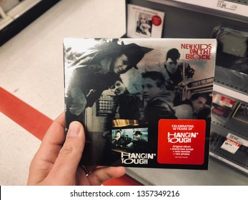 Minneapolis, MN - April 2, 2019: Caucasian woman shopper's hand holds a compact disc CD of the New Kids on the Block Hangin' Tough 30th Anniversary Edition of the album