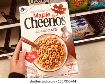 Minneapolis, MN - April 2, 2019: Caucasian woman shopper's hand holds a box of Maple Cheerios inside of a grocery store. Product produced by General Mills company