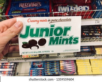 Minneapolis, MN - April 3, 2019: Caucasian woman shopper's hand holds up a box of Junior Mints chocolate candy while shopping in a grocery store