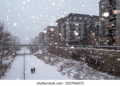 MINNEAPOLIS, MN - DECEMBER 2020 - A Wide Angle Shot of People on a Walk during a Winter Snowfall in the Uptown Neighborhood of South Minneapolis