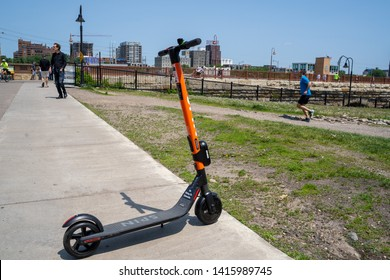 Minneapolis, MN - June 2, 2019: A Spin brand dockless, electric shared scooter parked on a sidewalk in Mill Ruins Park, waiting for its next rider