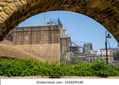 Minneapolis, MN - June 2, 2019: Stone Arch Bridge frames the St. Anthony Falls Lock and Dam on the Mississippi River in downtown Minneapolis
