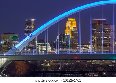 MINNEAPOLIS, MN - MARCH 2018 - A Telephoto Close Up Shot of Minneapolis Skyscrapers Behind Long Exposure Traffic on the Blue Lowry Bridge at Night