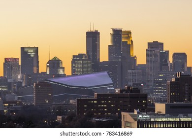MINNEAPOLIS, MN - OCTOBER 2017 - A Telephoto Shot Compressing Part of the University with the new US Bank Stadium and Downtown Minneapolis against a Clear Golden Sunset in Fall