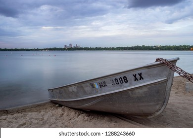 MINNEAPOLIS, MN - SUMMER 2018 - A Wide Shot of a Boat Moored at a Bde Maka Ska Beach looking toward the Distant Minneapolis Skyline during a Summer Dusk