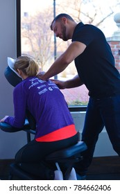 Minneapolis, MN / USA - 02.20.16:  Demonstration of chiropractic care. seated example, back massage, spinal care