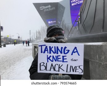 Minneapolis, MN/USA January 14, 2018- Protester holds a sign as part of the playoffs national anthem protest at US Bank Stadium.