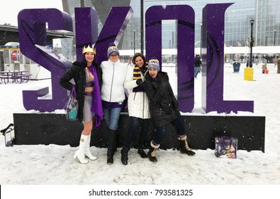 Minneapolis, MN/USA- January 14, 2018. -A group of Viking fans pose in front of the giant SKOL sign in front of US Bank Stadium before the Saints playoff game.