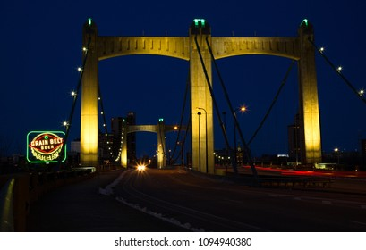 MINNEAPOLIS-MINNESOTA, APRIL 1, 2018:  a 48-foot-high sign with the Grain Belt logo, illuminated by a mix of neon tubes and incandescent bulbs next to the Hennepin Avenue Bridge in Minneapolis