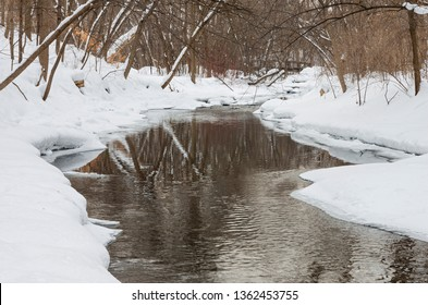 minnehaha creek flowing through snow covered forest of minnehaha parkway in minneapolis minnesota