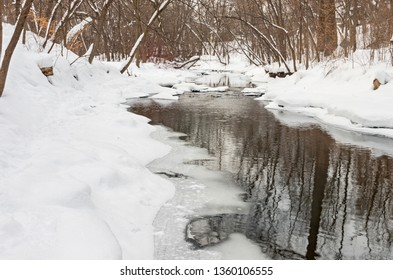 minnehaha creek and forest blanketed with fresh snow during winter in minneapolis minnesota