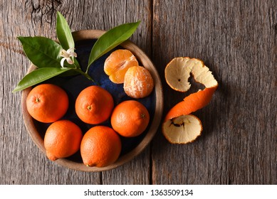 Minneola Tangelos: Closeup of peeled fruit on a plate with leaves and orange blossom on a rustic wood table.