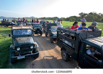 MINNERIYA, SRI LANKA - AUGUST 08, 2016 : A convoy of safari jeeps carrying tourists parked adjacent to the tank or man-made reservoir at Minneriya National Park in the late afternoon.