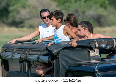 MINNERIYA, SRI LANKA - AUGUST 08, 2016 : Foreign tourists aboard a safari jeep observe a herd of wild elephants within Minneriya National Park in central Sri Lanka in the afternoon.