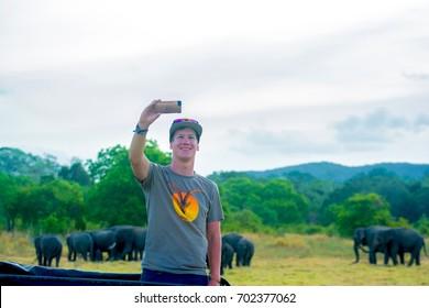 MINNERIYA, SRI LANKA – AUGUST 15: Tourists are watching wild elephants from safari jeeps in Minneriya National Park on August 15 2017 in Minneriya, Sri Lanka