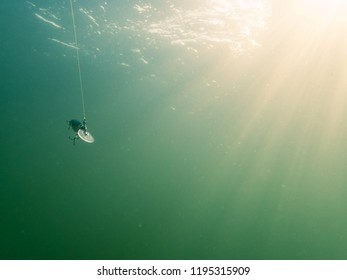 Minnow fishing lure swimming underwater, sunrays and water surface in the background.
