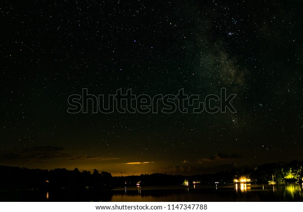 Minocqua, Wisconsin / United States - August 12, 2017:  Long exposure of a starfilled night sky over looking Lake Tomahawk in Minocqua, WI.
