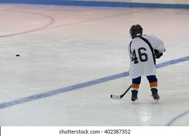 Minor ice hockey child skates with the puck in an arena during a practice drill