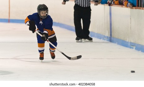 Minor ice hockey child skating after the puck during a game