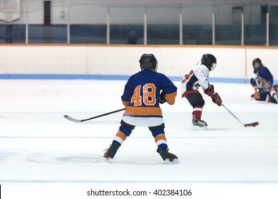 Minor ice hockey game action with kids