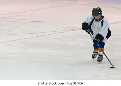 Minor ice hockey kid skates with the puck in an arena during a game