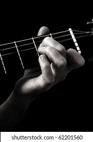 Minor seventh chord (Am7) on classical guitar; toned monochrome image