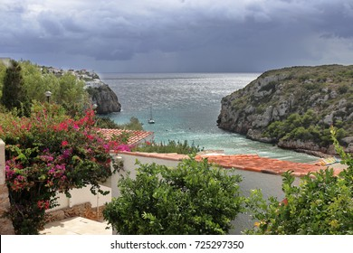 The Minorcan resort of Cala en Porter in the Mediterranean sea with stormy clouds