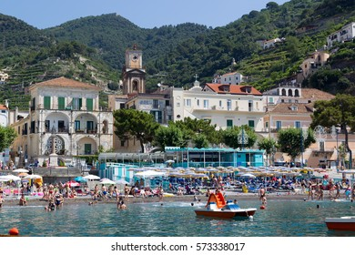 Minori, Italy, July 2, 2016: Many tourists sunbathing and swimming on the beach in Minori village. Sea view.