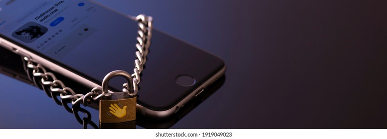 Minsk, Belarus - 01 31 2021: Browsing the Clubhouse app on a smartphone, a controversy of 2021 hiding behind the Social app. Lock on the phone as a symbol of a closed application.
