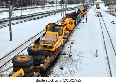 Minsk, Belarus - 02/19/2019: Transportation of dump trucks Belaz by rail. Heavy yellow mining truck disassembled on a railway platform. Logistics of cargo delivery by train