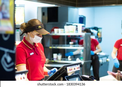 Minsk, Belarus 03.10.2020: McDonald's employee at the cash register wearing a mask and gloves during a pandemic