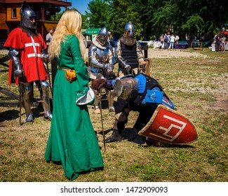 Minsk, Belarus – 05.26.2018: knight in medieval blue and black clothes and armor knelt in front of a beautiful lady in a green dress, the reconstruction of the knight tournament.