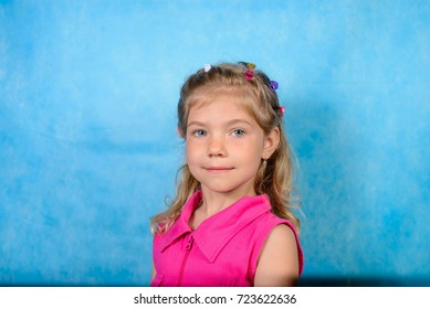 Minsk, Belarus - 1 September, 2017: portrait of a preschool girl 5-6 years old on a blue background