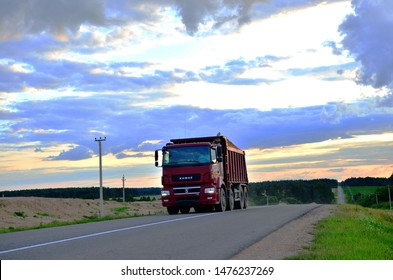 Minsk, Belarus 16.07.2019:  KAMAZ - 65801-001-68 (T5) dump truck (8x4)transports sand along the highway against the backdrop of sunset and beautiful countryside landscape