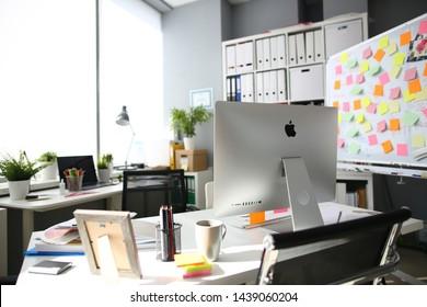 Minsk, Belarus - 28 June 2019: Apple imac computer aganist empty office background. Illustrtive editorial image.