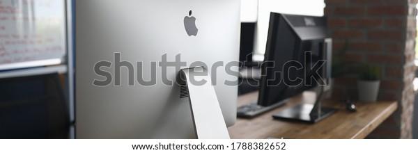 Minsk, Belarus - 29 May 2020: Apple Imac pc against empty office background. Illustrative editorial