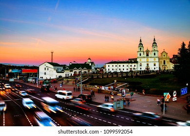 Minsk, Belarus. Aerial view of Minsk Cathedral with people and car traffic in Belarus. Car trail lights and sunset sky.