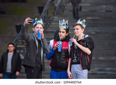 Minsk, Belarus - Apr 03, 2017. Three guys do selfie with a crown and soda from fast food in their hands. ?ompany drinks soda from Burger King`s paper glasses. Teenagers love selfie.