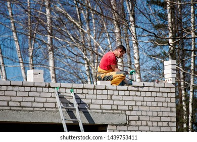 Minsk, Belarus - Apr 2019. Bricklayer working on new building. Worker behind work. Brick masonry construction. Construction worker installing white brick masonry on exterior wall with  putty knife