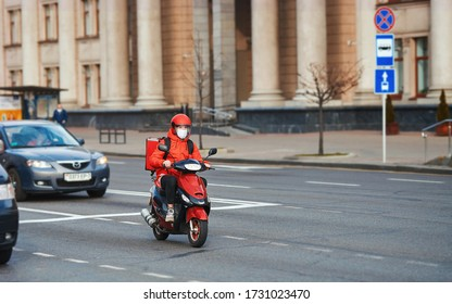 Minsk, Belarus. Apr 2020. Delivery boy in protective mask on moto scooter delivering online food orders to customers on city street. Young delivery boy with red backpack, food courier
