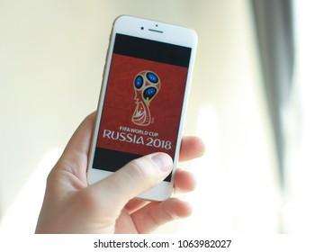 MINSK, BELARUS – April 07, 2018: Woman holding brand new white Apple iPhone 7. The official logo of the football World Cup in Russia 2018.